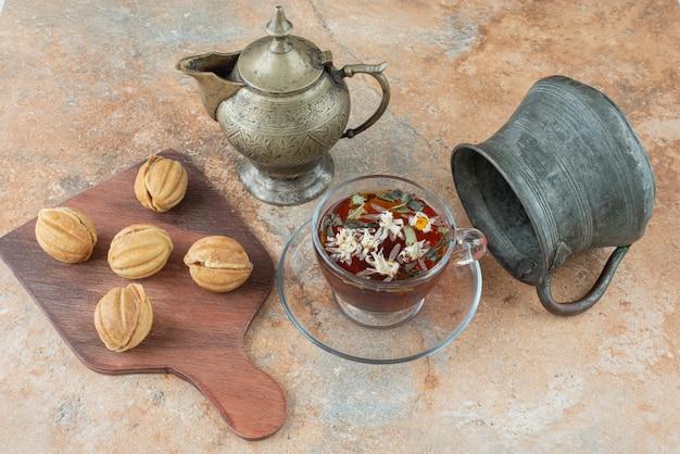 Zwei alte teekannen mit süßen keksen auf marmorhintergrund
