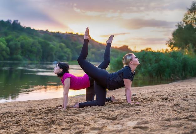 Zwei anmutige junge frau, die synchronisierten yoga tut