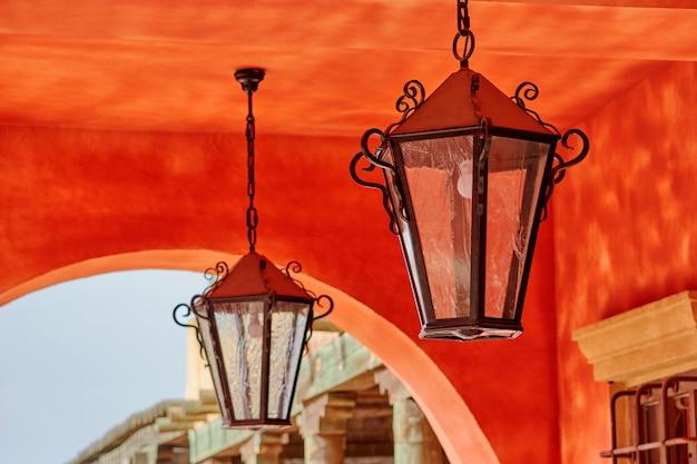 Zwei antike glas- und metalllaternen, die in einem haus mit roter fassade hängen. madrid, spanien