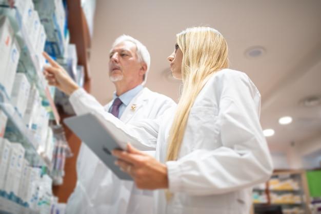 Zwei apotheker überprüfen ihr inventar in ihrer apotheke