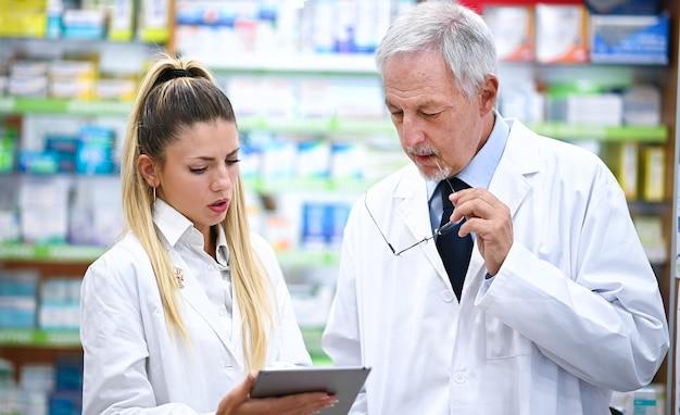 Zwei apotheker unterhalten sich während der arbeit an einem tablet in ihrem geschäft