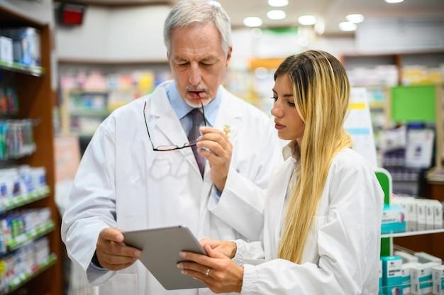 Zwei apotheker unterhalten sich, während sie in ihrem geschäft an einem tablet arbeiten