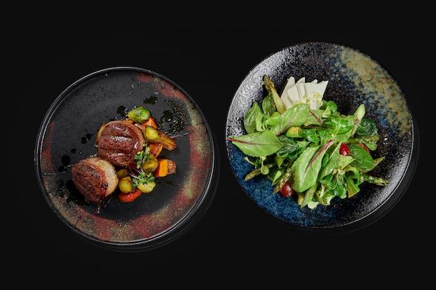 Zwei appetitliche gerichte - salat mit feta-käse und tomaten sowie rindersteaks in stilvollen keramikplatten auf schwarzer oberfläche. draufsicht. lebensmittelfoto für menü