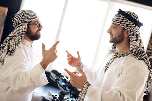 Zwei araber nähern sich dem teleskop, das auf einander schaut.
