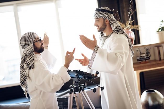 Zwei araber nähern sich dem teleskop, das auf einander schaut