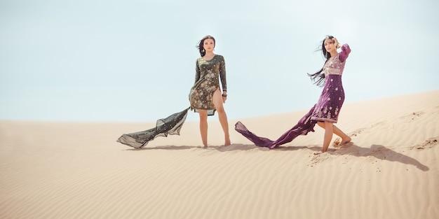 Zwei arabische frauen in der nationalen kleidung, die in der wüste reist.