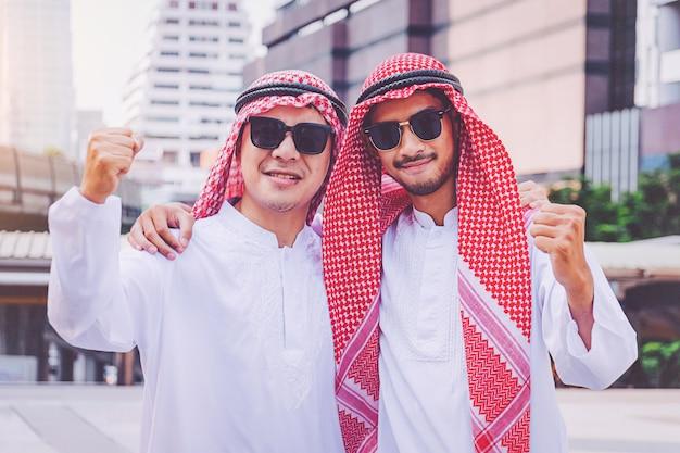 Zwei arabische geschäftsmänner, die stehen, indem sie beide hände in der stadt anheben