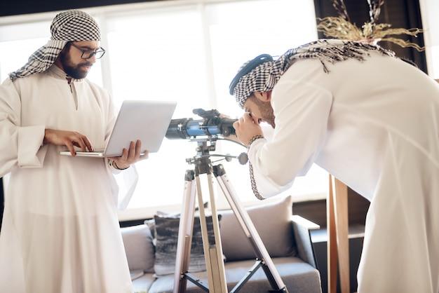 Zwei arabische geschäftsmänner mit laptop und teleskop am hotelzimmer