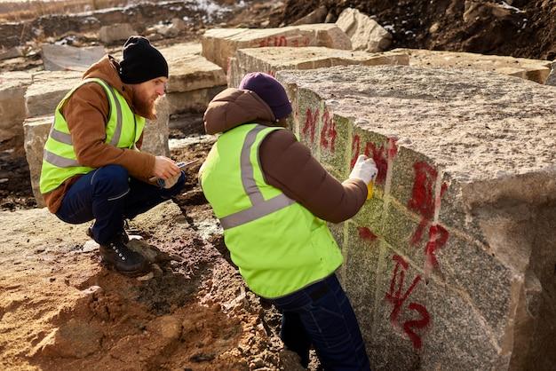Zwei arbeiter, die granitblöcke markieren