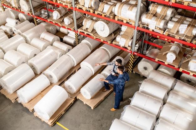 Zwei arbeiter eines großen fabriklagers entscheiden, welcher teil der neuen produktion an partner verkauft werden kann