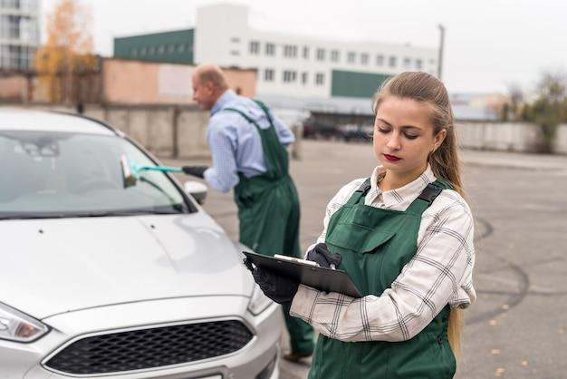 Zwei arbeiter im autoservice posieren in der nähe des autos