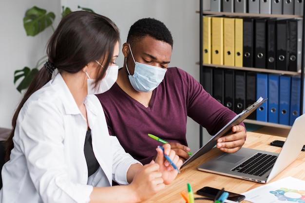 Zwei arbeiter im büro während der pandemie tragen medizinische masken