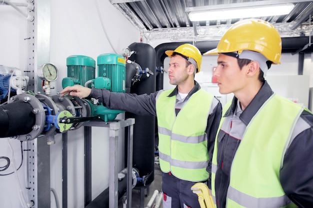 Zwei arbeiter in schutzhelmen im werk, die die druckparameter überprüfen
