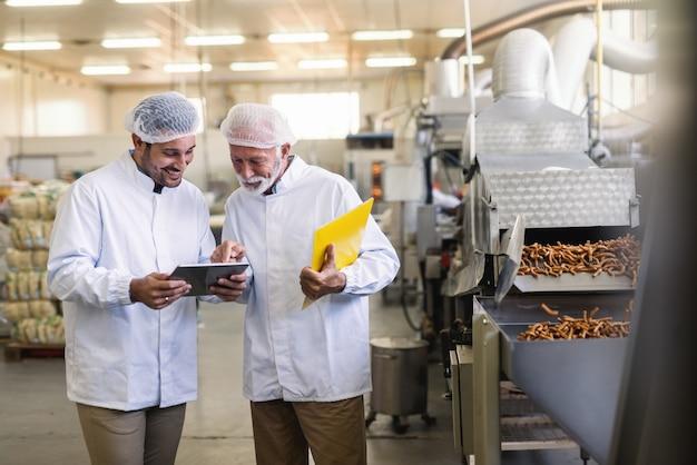Zwei arbeiter in uniformen, die tablette betrachten, während sie in der lebensmittelfabrik stehen. älterer zeigt auf tablette.