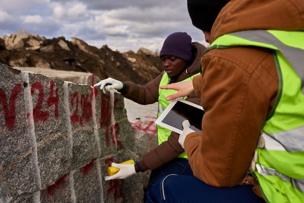 Zwei arbeiter markieren granit