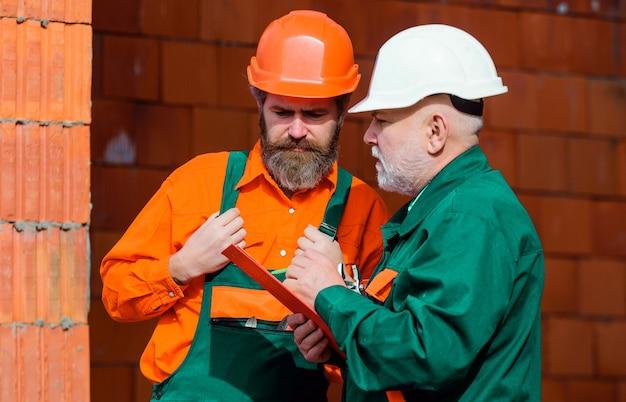 Zwei arbeiter mit helmen und baumeisteruniform auf der baustelle. professionelle baumeister bei der arbeit.