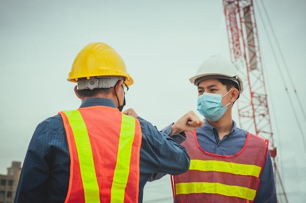 Zwei arbeiter schütteln die ellbogen