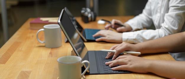Zwei arbeiterinnen arbeiten an ihrem projekt mit digitalem tablet, während sie zusammen im büroraum sitzen