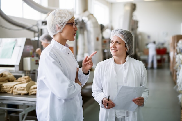 Zwei arbeiterinnen diskutieren, während sie in der lebensmittelfabrik stehen.