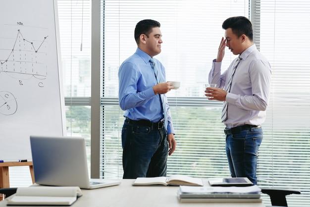 Zwei arbeitskollegen diskutieren die arbeitsbelastung bei einer tasse kaffee