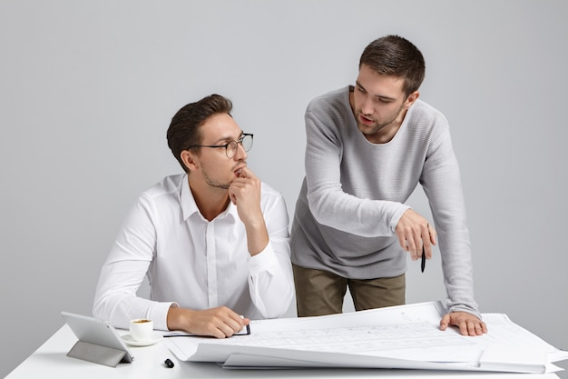 Zwei architekten diskutieren bauprojekt. junger unerfahrener mann bittet um rat