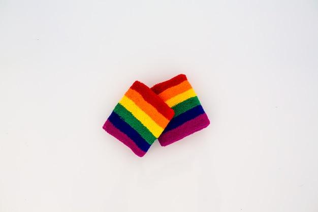 Zwei armbänder, zum mit der schwulen stolzflagge auf weißem hintergrund laufen zu gehen
