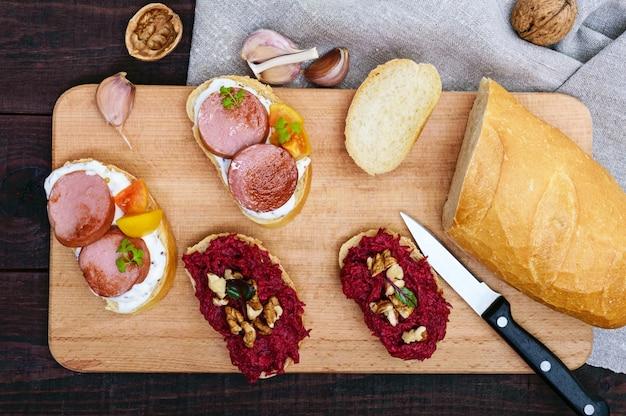 Zwei arten von frühstücksbrötchen mit gegrillten würstchen und gelben tomaten sowie gekochten geriebenen rüben und walnüssen