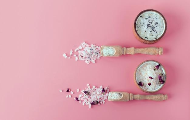 Zwei arten von himalaya-bade- und spa-öko-salzen. spa-behandlung. die industrie der entspannung. badekristalle in einer holzplatte. flach lag auf einem rosa hintergrund mit kopierraum banner. kein verlust. rose, lavendel