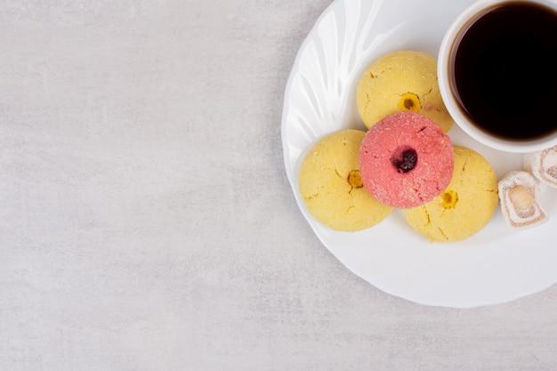 Zwei arten von keksen, köstlichkeiten und eine tasse tee auf weißem teller.