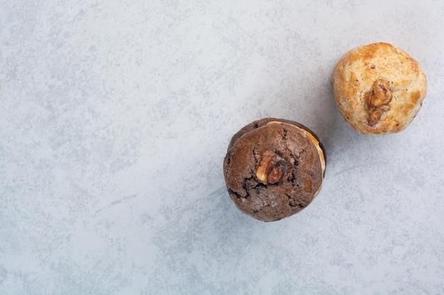 Zwei arten von keksen mit walnuss auf grauem hintergrund. foto in hoher qualität