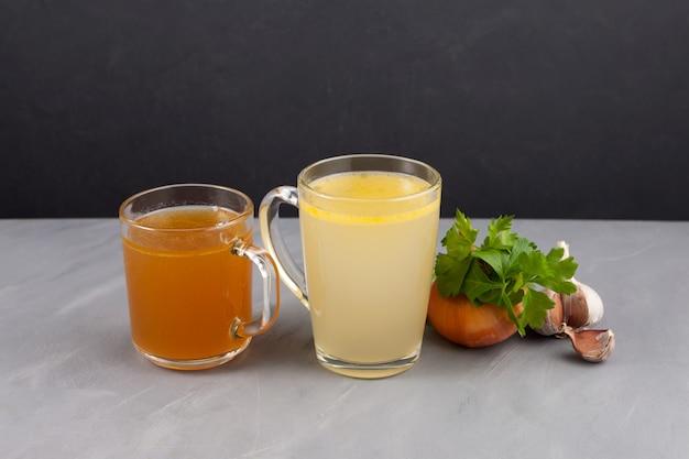 Zwei arten von knochenbrühe (gelb und braun) in transparenten bechern. fisch- und fleischbrühe enthalten gesundes kollagen.