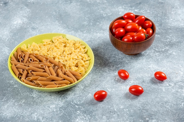 Zwei arten von rohen nudeln auf teller mit schüssel tomaten.