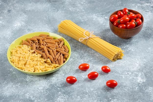 Zwei arten von rohen nudeln auf teller mit tomaten und spaghetti.