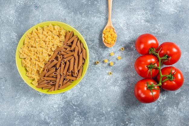 Zwei arten von rohen nudeln auf teller mit tomaten.