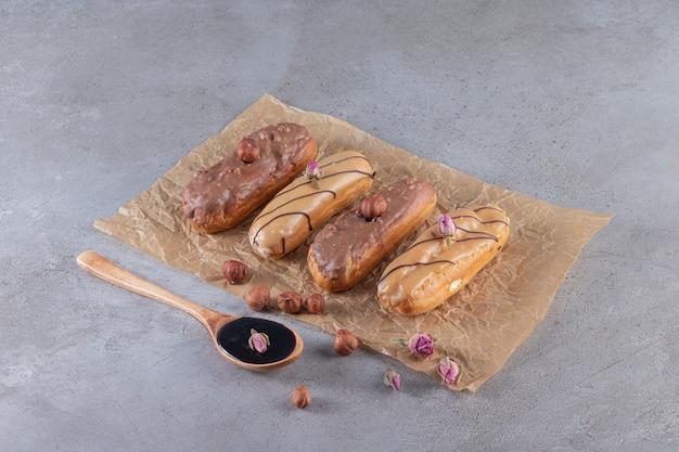 Zwei arten von schokoladen-eclairs mit einem löffel schokolade auf einer steinoberfläche