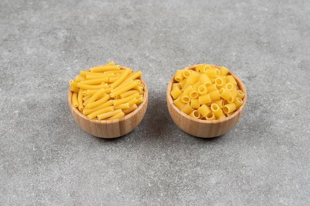 Zwei arten von ungekochten makkaroni auf marmoroberfläche