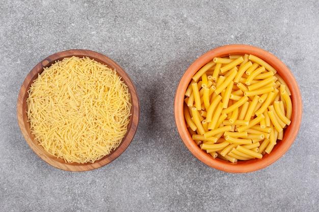 Zwei arten von ungekochten nudeln in holzschalen