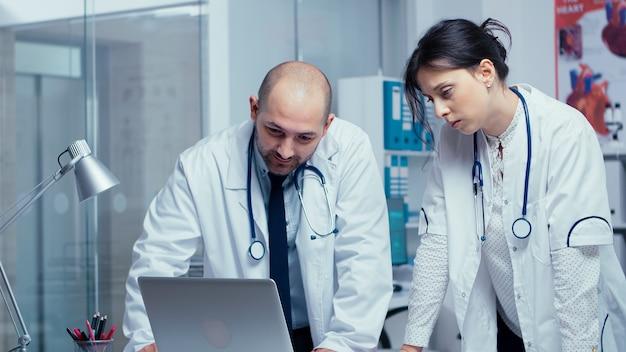 Zwei arztkollegen, die sich über ein medizinisches problem nicht einig sind, während sie auf den laptop schauen und darüber sprechen. gesundheitssystem, private moderne medizinische krankenhausklinik