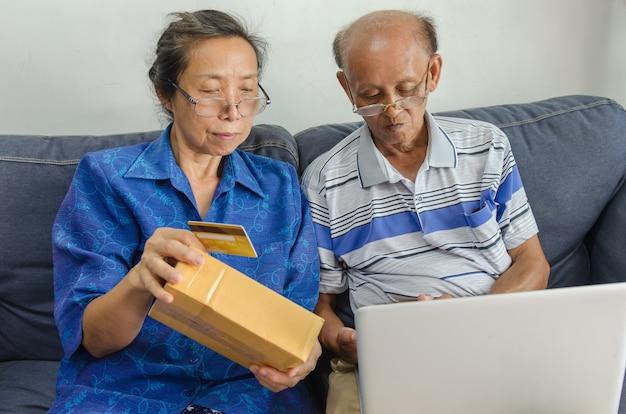 Zwei asiatische ältere leute, die online einkaufen. senior hält kreditkarte, die auf einem sofa mit laptop zu hause sitzt.