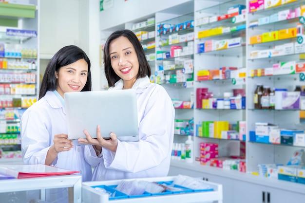 Zwei asiatische apotheker arbeiten in einer apotheke mit einem laptop. gesundheitsversorgung und medizinisches konzept.