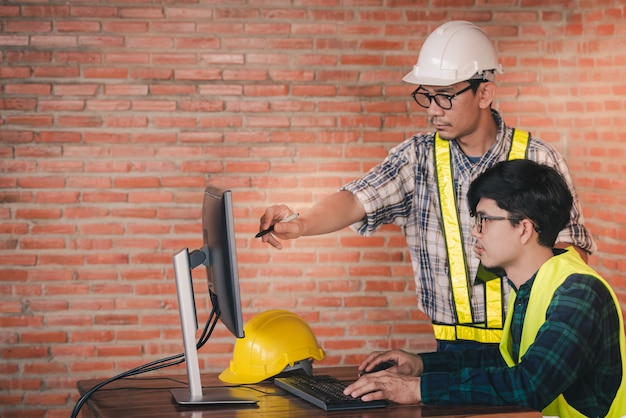 Zwei asiatische bauingenieure und architekten sprechen über informationsarbeit und das zeichnen auf computern in architekturprojekten auf den baustellen an den schreibtischen.