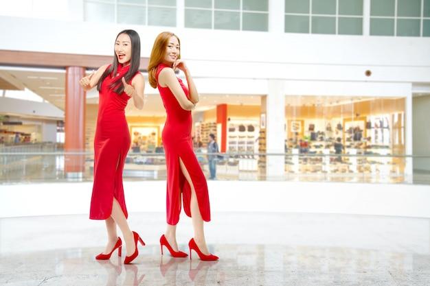 Zwei asiatische chinesinnen im cheongsam kleid feiern chinesisches neujahr
