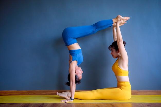 Zwei asiatische frau, die yoga im blauen hintergrund tut.