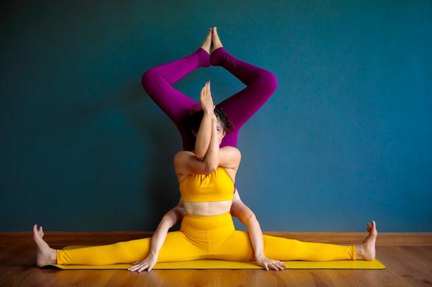 Zwei asiatische frau, die yoga-pose im hauptwohnzimmer tut