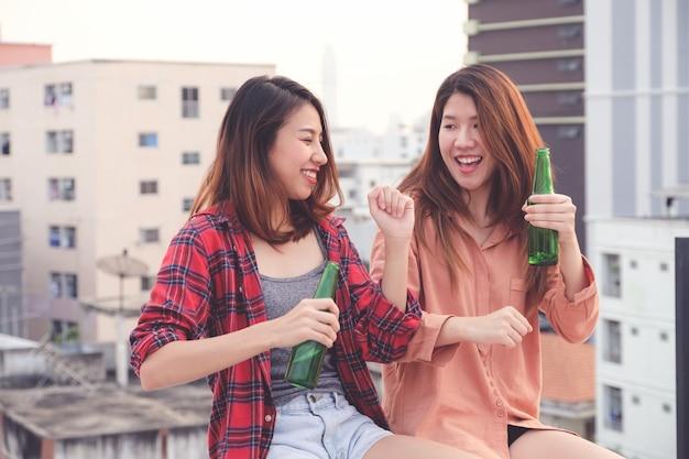 Zwei asiatische frauen, die an der dachspitzenparty draußen feier, freundschaft, lgbt-paar trinken