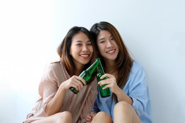 Zwei asiatische frauen, die bier an der partei, feier, lgbt-paar, lebensstil trinken
