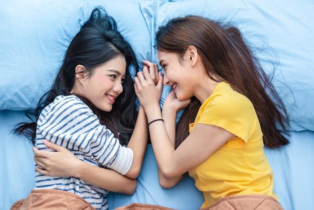 Zwei asiatische frauen, die einander beim lügen auf bett betrachten
