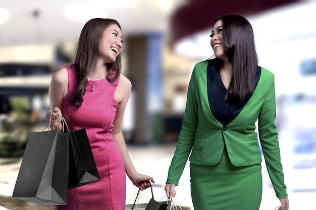 Zwei asiatische frauen, die einkaufstaschen im mall tragen