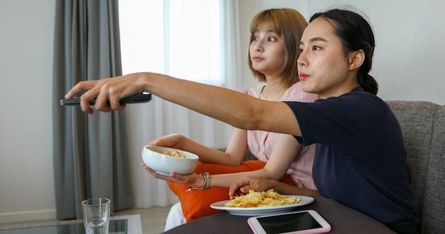 Zwei asiatische frauen, die fernbedienung zum öffnen verwenden und fernsehen. sie essen snacks auf dem sofa zu hause und lachen an urlaubstagen.