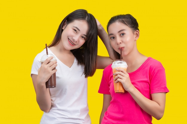 Zwei asiatische frauen, die gefrorenen milchtee und gefrorenen kakao auf einem gelb trinken.